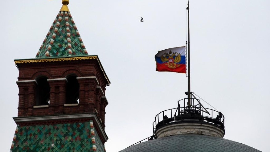 The Russian national flag is flown at half-mast on top of the Senate Building in Kremlin on the day of national mourning in Moscow, Russia, Sunday, Nov. 1, 2015. The Russian Metrojet airliner crashed Saturday in a remote mountainous part of Egypt's Sinai Peninsula 23 minutes after taking off from a popular Red Sea resort, killing all 224 people on board, including 25 children. (AP Photo/Pavel Golovkin)