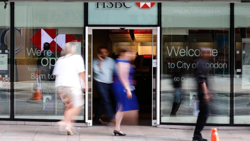 FILE - This is a Friday, Aug. 28, 2015 file photo of people as they walk past a branch of HSBC bank in London. HSBC's pre-tax profit has jumped by a third in the latest quarter as it paid out less in fines, settlements and British customer compensation ordered by regulators, the bank said Monday Nov. 2, 2015. The bank, Europe's largest by market value, posted $6.1 billion in profit for the July-September period, up 32 percent from a year earlier.  Revenue slipped 4 percent to $15.1 billion. (AP Photo/Frank Augstein, File)