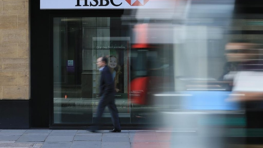 A bus drives past a branch of HSBC near Liverpool Street Station in London, Monday Nov. 2, 2015 as the bank on Monday  announced that their pre-tax profit has jumped by a third in the latest quarter. The bank, Europe's largest by market value, posted $6.1 billion in profit for the July-September period, up 32 percent from a year earlier, as it paid out less in fines, settlements and British customer compensation ordered by regulators. (AP Photo/Tim Ireland)