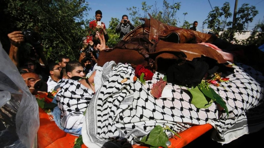 Palestinians carry the body of Raed Jaradat, 22, at the family house during his funeral in the West Bank village of Sa'ir, Hebron, Sunday, Nov. 1, 2015. According to the Israeli military, Jaradat stabbed an Israeli in the neck Monday, Oct. 26, before being shot and killed. (AP Photo/Nasser Shiyoukhi)