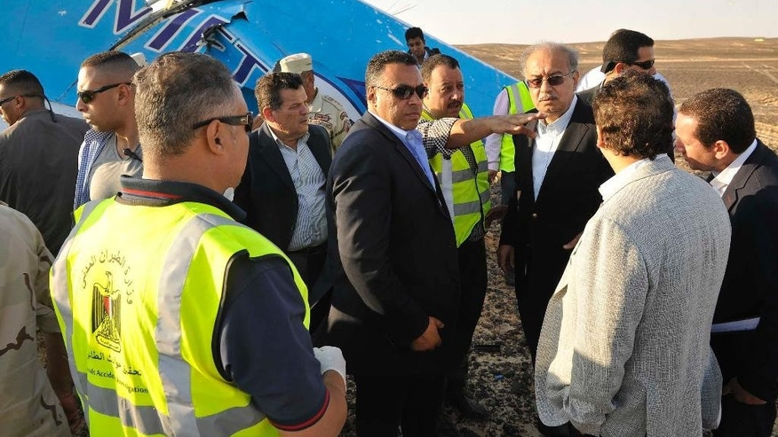 CORRECTS DAY OF WEEK TO SATURDAY, NOT FRIDAY - In this photo released by the Prime Minister's office, Sherif Ismail, third right, and military and government officials visit the site where a passenger plane crashed in Hassana, Egypt on Saturday, Oct. 31, 2015. The Russian aircraft carrying 224 people crashed Saturday in a remote mountainous region in the Sinai Peninsula about 20 minutes after taking off from a Red Sea resort popular with Russian tourists, the Egyptian government said. There were no survivors. (Suliman el-Oteify/Egyptian Prime Minister's Office via AP)