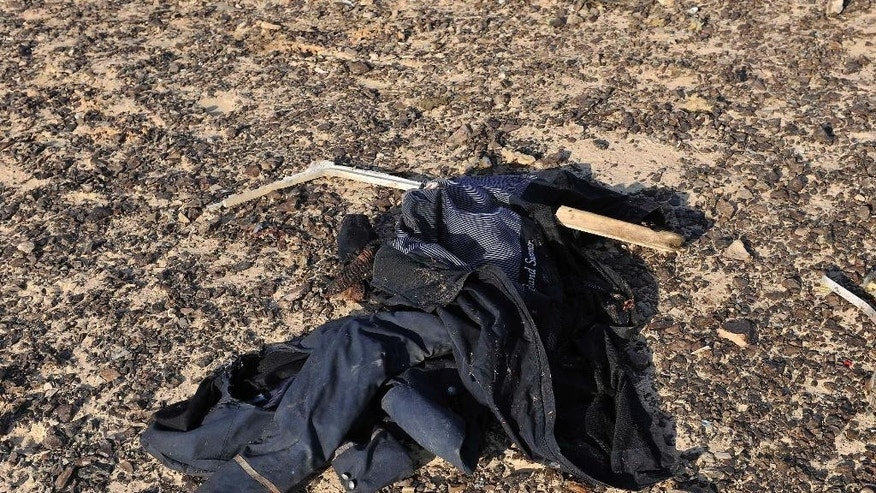CORRECTS DAY OF WEEK TO SATURDAY, NOT FRIDAY - In this photo released by the Prime Minister's office, an item, of clothing lies at the site where a passenger plane crashed in Hassana, Egypt on Saturday, Oct. 31, 2015. A Russian aircraft carrying 224 people crashed Saturday in a remote mountainous region in the Sinai Peninsula about 20 minutes after taking off from a Red Sea resort popular with Russian tourists, the Egyptian government said. There were no survivors. (Suliman el-Oteify/Egyptian Prime Minister's Office via AP)