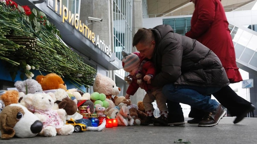 People lay flowers and toys at an entrance of Pulkovo airport outside St.Petersburg, Russia, during a day of national mourning for the plane crash victims, on Sunday, Nov. 1, 2015. The Russian Metrojet airliner crashed Saturday in a remote mountainous part of Egypt's Sinai Peninsula 23 minutes after taking off from a popular Red Sea resort, killing all 224 people on board, including 25 children. (AP Photo/Dmitry Lovetsky)