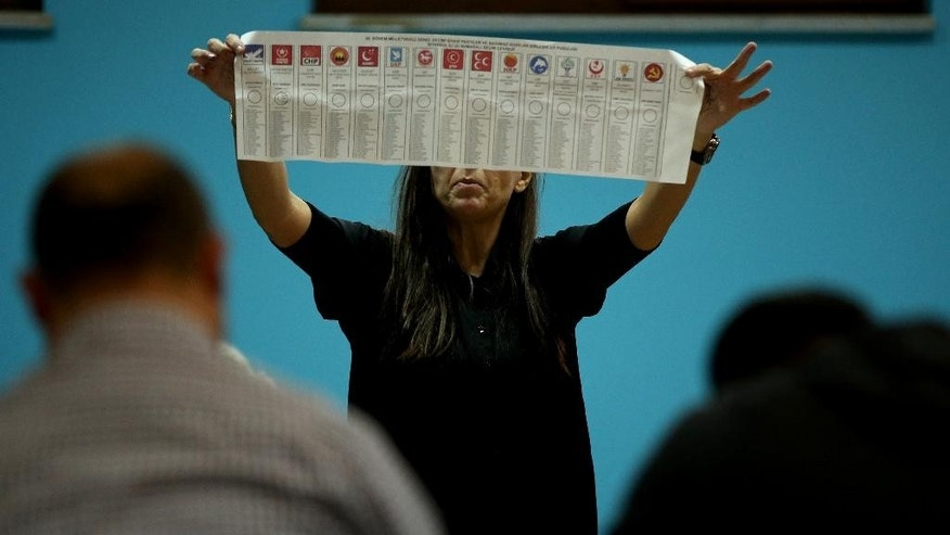 A Turkish election official shows a ballot paper with signs of 15 political parties participating in election, as she counts ballots shortly after the polling stations closed at the end of the election day, in Istanbul, Sunday, Nov. 1, 2015. Turks headed to the polls Sunday for the second time in five months in what is being seen as a crucial general election that will determine whether the ruling party can restore the parliamentary majority it enjoyed for the past 13-years. (AP Photo/Hussein Malla)