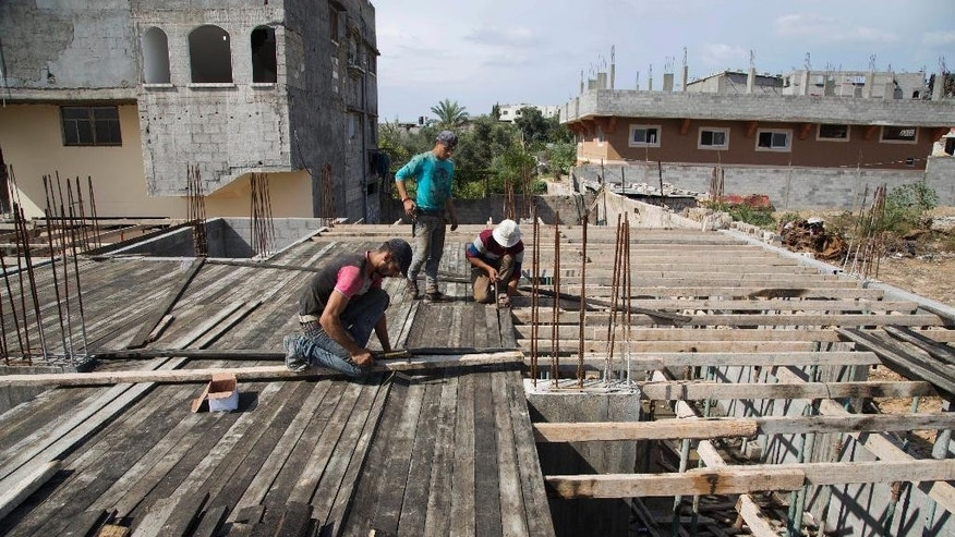 In this Wednesday, Oct. 28, 2015 photo, Palestinians work on rebuilding a house which was destroyed  during the last summer's war between Israel and Hamas, Gaza City. The four story house belonging to al-Zaza family is being rebuilt ad part of the family has moved in into renovated ground floor apartment.  (AP Photo/Adel Hana)