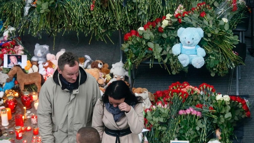 A couple react as they come to lay flowers and toys at an entrance of Pulkovo airport outside St.Petersburg, Russia, during a day of national mourning for the plane crash victims, on Sunday, Nov. 1, 2015. Hundreds of people are bringing flowers and pictures to St. Petersburg's airport to commemorate the 224 victims of the Russian plane crash in Egypt. (AP Photo/Dmitry Lovetsky)