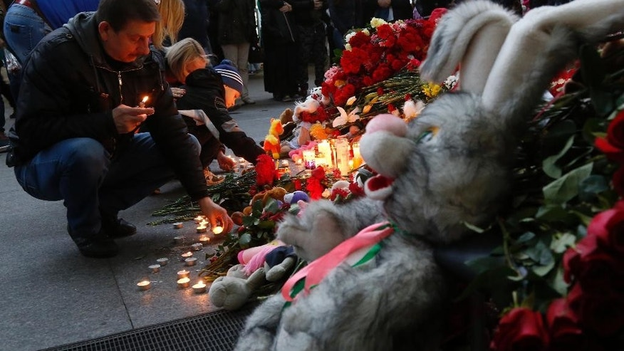 People lay flowers, toys and light candles at an entrance of Pulkovo airport outside St.Petersburg, Russia, during a day of national mourning for the plane crash victims, on Sunday, Nov. 1, 2015. Hundreds of people are bringing flowers and pictures to St. Petersburg's airport to commemorate the 224 victims of the Russian plane crash in Egypt. (AP Photo/Dmitry Lovetsky)