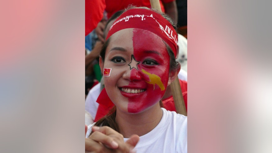 A supporter with her face painted in the flag of Myanmar opposition leader Aung San Suu Kyi's National League for Democracy party applauds as she listens speech of their leader during an election campaign rally for upcoming general election Sunday, Nov 1, 2015, in Yangon, Myanmar. Myanmar's general elections are scheduled for Nov. 8, the first since a nominally civilian government was installed in 2011. (AP Photo/Khin Maung Win)