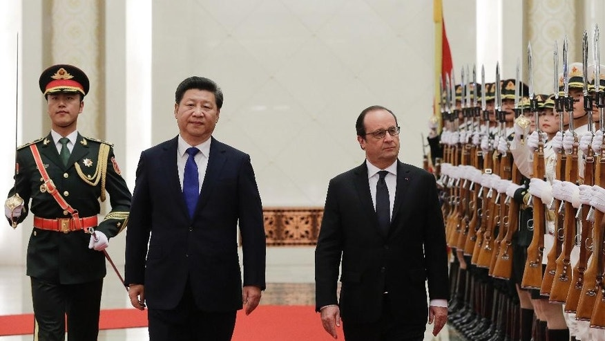 French President Francois Hollande, right, and Chinese President Xi Jinping, second left, review an honor guard during a welcome ceremony at the Great Hall of the People in Beijing, China, Monday, Nov. 2, 2015. (AP Photo/Andy Wong)