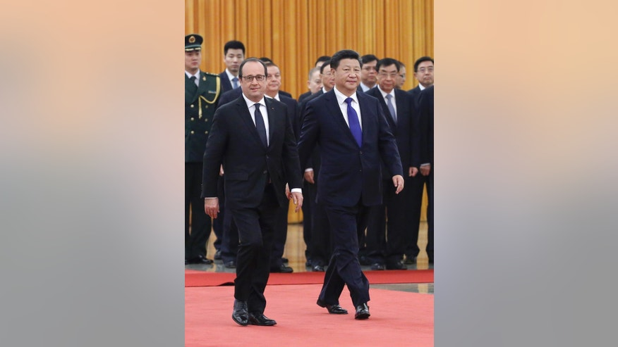 French President Francois Hollande, left, walks with Chinese President Xi Jinping as they arrive for a welcome ceremony at the Great Hall of the People in Beijing, China, Monday, Nov. 2, 2015. (AP Photo/Andy Wong)