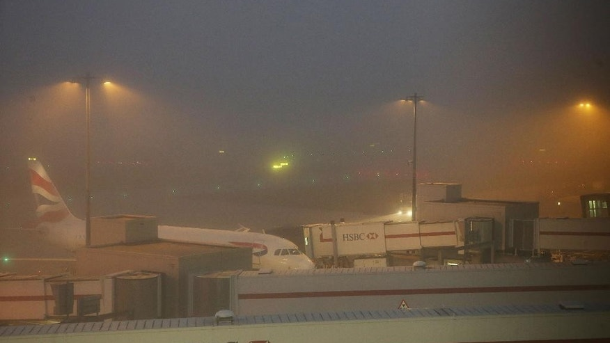 A British Airways plane stands on the ground at Heathrow Airport Terminal 5, as some dozens of flights have been canceled at the airport due to thick fog in the area, Sunday Nov. 1, 2015. A spokeswoman for Britain's busiest airport said the weather had forced the cancellation of about 50 flights and advised passengers caught up in the disruption to contact their airlines. (Steve Parsons / PA via AP) UNITED KINGDOM OUT - NO SALES - NO ARCHIVES