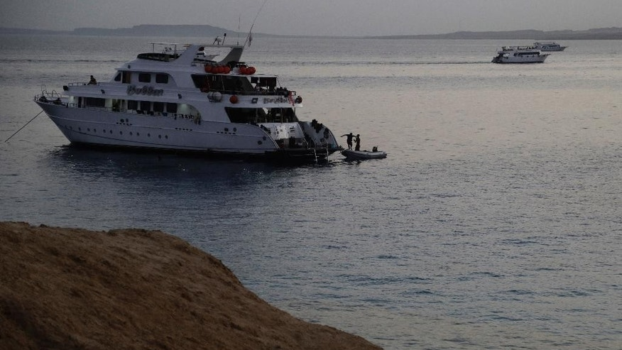 In this Oct. 13, 2015 photo, divers prepare to enter the Red Seas as the sun sets in Sharm el-Sheik, south Sinai, Egypt. As Egypt's tourism sector slowly recovers from years of political tumult that left it battered, Russians have emerged as the dominant group on its Red Sea beaches, and it was here that over 200 of them had their final getaway before perishing in Saturday's airline disaster. (AP Photo/Thomas Hartwell)