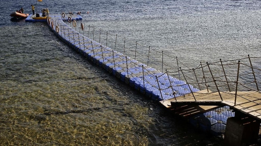 In this Oct. 13, 2015 photo, swimmers use a floating bridge to access the coral reef on the Red Sea at Sharm el-Sheik, south Sinai, Egypt. As Egypt's tourism sector slowly recovers from years of political tumult that left it battered, Russians have emerged as the dominant group on its Red Sea beaches, and it was here that over 200 of them had their final getaway before perishing in Saturday's airline disaster. (AP Photo/Thomas Hartwell)