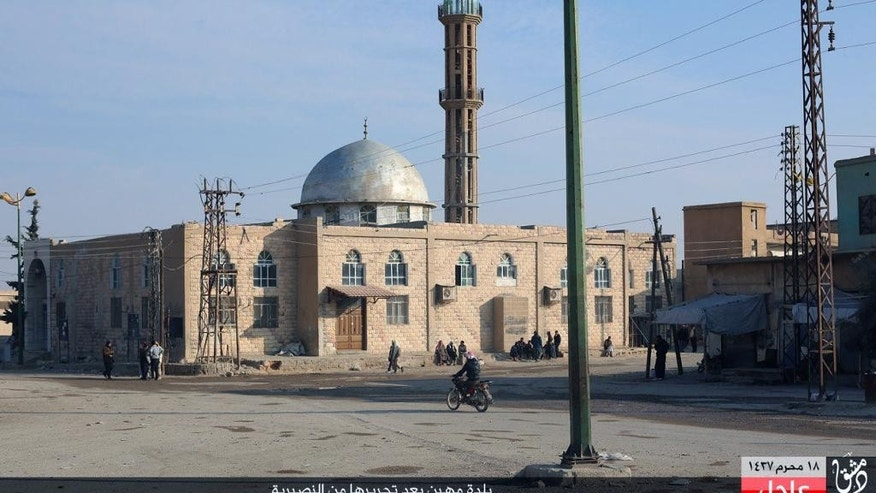 "This image posted on Sunday, Nov. 1, 2015, by a website used by Islamic State militants, shows Syrians in front of a mosque in the village of Mahin, central Homs province, Syria. The Islamic State militant group is advancing in central Syria, seizing control of a town that lies near a highway leading to the capital, Damascus, and attacking another, activists and the group said Sunday. The Arabic at the bottom reads, ""The village of Mahin after it was liberated from the Alawites."" (Islamic State militant website via AP)"