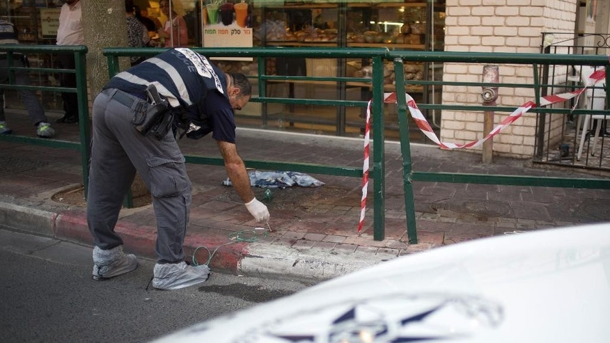 An Israeli police officer of the forensic unit collects blood at a stabbing attack in Rishon Lezion, Israel, Monday, Nov. 2, 2015. Israel's emergency rescue service said two people were seriously injured and one lightly in the attack in Rishon Lezion near Tel Aviv. (AP Photo/Ariel Schalit)