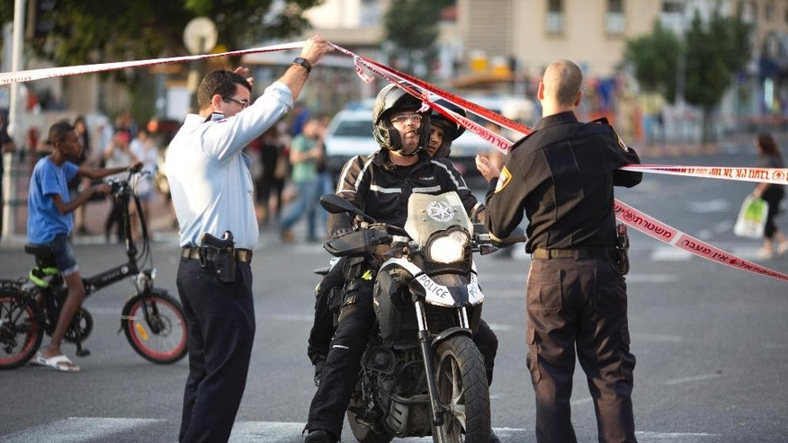 Israeli police officer cordon the site of a stabbing attack in Rishon Lezion, Israel, Monday, Nov. 2, 2015.  Israel's emergency rescue service said two people were seriously injured and one lightly in the attack in Rishon Lezion near Tel Aviv. (AP Photo/Ariel Schalit)