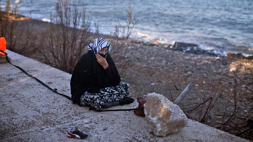 A women rests at a beach after she disembarked from a small boat on the northern shore of Lesbos, Greece, Monday, Nov. 2, 2015. The number of smuggling boats crossing over to Greece from the nearby Turkish coast fell in the last days as strong winds raked the eastern Aegean Sea, but some still attempted the dangerous crossing. (AP Photo/Marko Drobnjakovic)