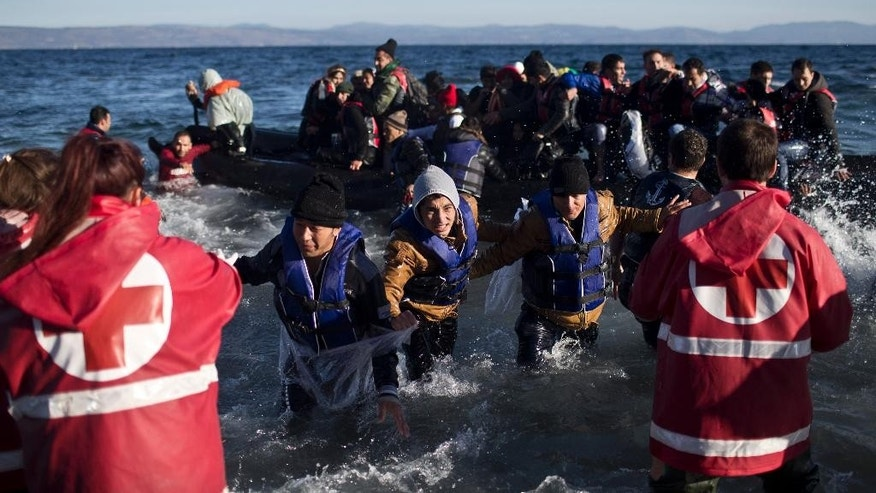 People rush to disembark from a rubber boat at a beach on the northern shore of Lesbos, Greece, Monday, Nov. 2, 2015. The number of smuggling boats crossing over to Greece from the nearby Turkish coast fell in the last days as strong winds raked the eastern Aegean Sea, but some still attempted the dangerous crossing. (AP Photo/Marko Drobnjakovic)
