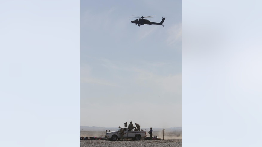 An Egyptian military helicopter flies over wreckage of the Metrojet passenger plane bound for St. Petersburg, Russia that crashed Saturday, in Hassana, Egypt,  Sunday, Nov. 1, 2015. The Russian jetliner that crashed shortly after takeoff from an Egyptian resort area broke up at high altitude, scattering fragments of wreckage over a wide area in the Sinai Peninsula, Russia's top aviation official said Sunday as search teams raced to recover the bodies of the 224 people who died. (AP Photo/Amr Nabil)