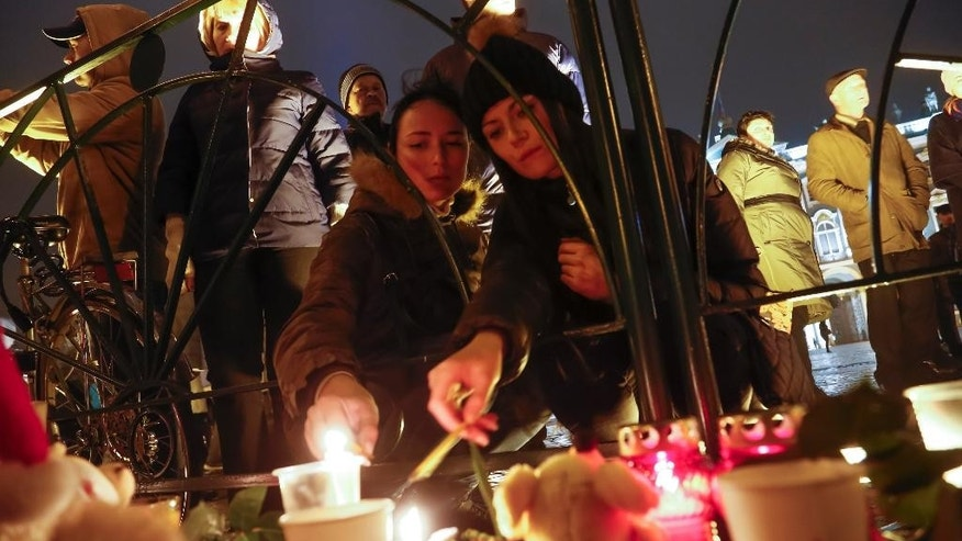 People light candles during a day of national mourning for the plane crash victims at Dvortsovaya (Palace) Square in St. Petersburg, Russia, on Sunday, Nov. 1, 2015. The Metrojet charter crashed Saturday morning 23 minutes after taking off from Egypt's Red Sea resort of Sharm el-Sheikh, a top destination for Russian tourists. All 224 people on board died.  (AP Photo/Dmitry Lovetsky)