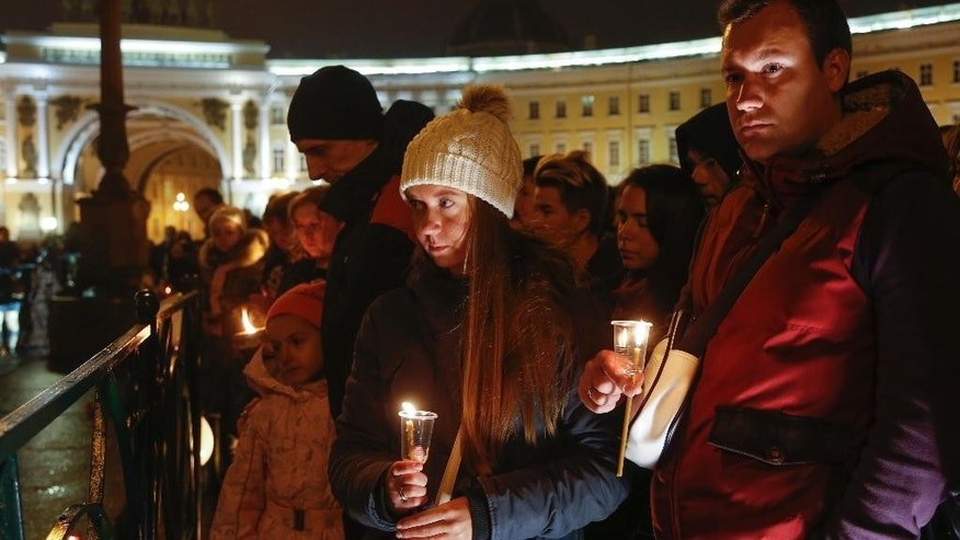 People hold candles during a day of national mourning for the plane crash victims at Dvortsovaya (Palace) Square in St. Petersburg, Russia, on Sunday, Nov. 1, 2015.  The Metrojet charter crashed Saturday morning 23 minutes after taking off from Egypt's Red Sea resort of Sharm el-Sheikh, a top destination for Russian tourists. All 224 people on board died.  (AP Photo/Dmitry Lovetsky)