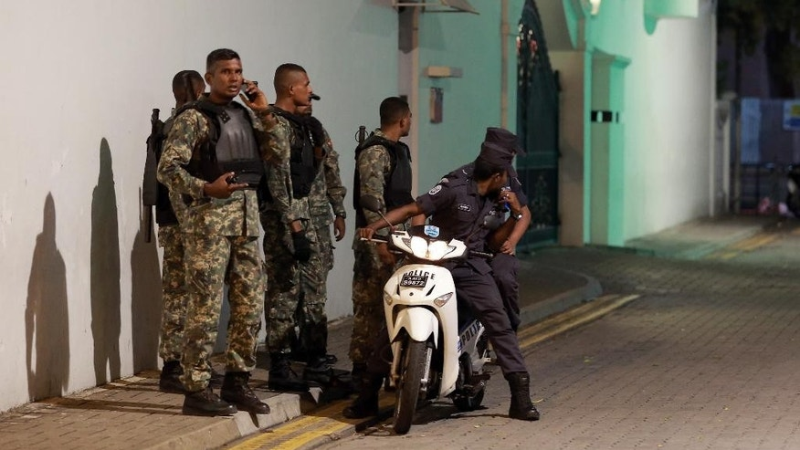 In this Monday, Nov. 2, 2015 photo, Maldivian security officers stand guard near the president's official residence where the military found and deactivated an explosive device in Male, Maldives. The discovery came a month after an explosion occurred on President Yameen Abdul Gayoom's boat, injuring his wife, an aide and a bodyguard.  (AP Photo/Mohamed Sharuhaan)