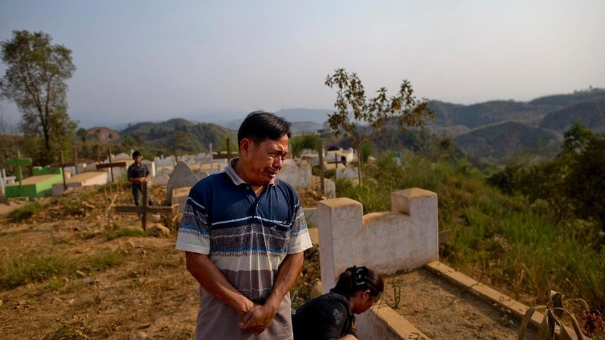 In this March 21, 2015, photo, Brang Shawng weeps during a visit to the grave of his daughter Ja Seng Ing, who was killed in what witnesses say was a burst of army gunfire in Hpakant Christian cemetery, Northern Kachin state, Myanmar. After hearing of his country's move towards a new civilian democracy, Brang Shawng sent a complaint letter to the military seeking justice and to his surprise spent the next two years himself appearing in court for daring to accuse the army of her murder. His ordeal reflects just how perilous the quest for justice in Myanmar can be, especially for ethnic minorities. (AP Photo)