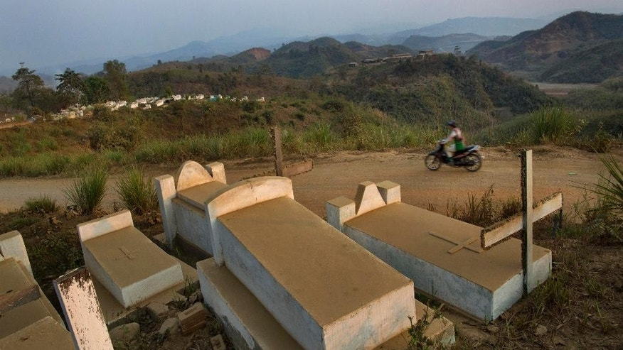 In this March 22, 2015 photo, a man rides a motorbike past Hpakant Christian cemetery where Ja Seng Ing, allegedly killed in army gunfire, is buried in Hpakant, Northern Kachin state, Myanmar. After hearing of his country's move towards a new civilian democracy, Brand Shawng, father of Ja Seng Ing, sent a complaint letter to the military seeking justice for her death and in return to his surprise spent the next two years himself appearing in court for daring to accuse the army of her murder. His ordeal reflects just how perilous the quest for justice in Myanmar can be, especially for ethnic minorities. (AP Photo)