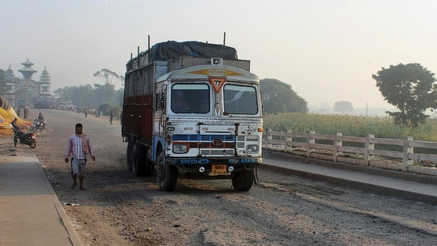 A man walks near a truck at Birgunj, a town on the border with India, Nepal, Monday, Nov. 2, 2015. Nepalese police removed protesters from a key border point Monday to allow more than 200 vehicles stranded for the past 40 days to cross into India, officials said. (AP Photo/Jiyalal Sah)