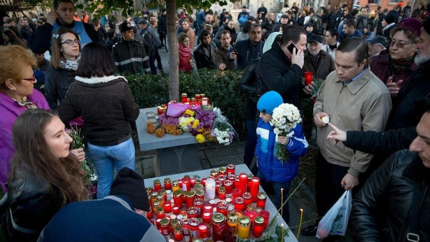 A child holds flowers as people light candles outside the Colectiv nightclub, during a mourning march joined by thousands in Bucharest, Romania, Sunday, Nov. 1, 2015. As the nation entered its second day of mourning, thousands paid their respects at the Colectiv nightclub in Bucharest's 4th district, scene of mayhem and tragedy Friday night when a fire engulfed the venue, causing a panic that killed tens of people and injured many others, raising serious questions about fire regulations and safety procedures in Romania. (AP Photo/Vadim Ghirda)