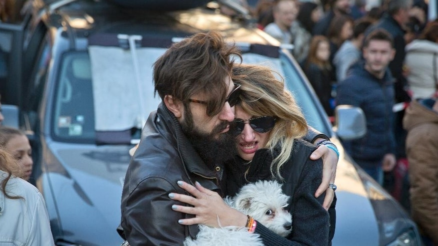 A woman cries as her partner comforts her outside the Colectiv nightclub, during a mourning march joined by thousands in Bucharest, Romania, Sunday, Nov. 1, 2015. As the nation entered its second day of mourning, thousands paid their respects at the Colectiv nightclub in Bucharest's 4th district, scene of mayhem and tragedy Friday night when a fire engulfed the venue, causing a panic that killed tens of people and injured many others, raising serious questions about fire regulations and safety procedures in Romania. (AP Photo/Vadim Ghirda)