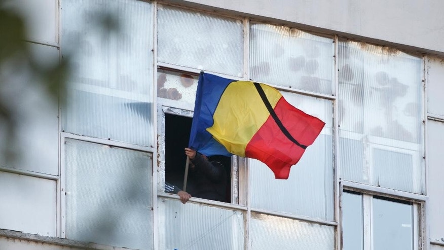 A Romanian flag with a black ribbon on it is waved from a window in the compound that housed the Colectiv nightclub, during a mourning march joined by thousands in Bucharest, Romania, Sunday, Nov. 1, 2015. As the nation entered its second day of mourning, thousands paid their respects at the Colectiv nightclub in Bucharest's 4th district, scene of mayhem and tragedy Friday night when a fire engulfed the venue, causing a panic that killed tens of people and injured many others, raising serious questions about fire regulations and safety procedures in Romania. (AP Photo/Vadim Ghirda)