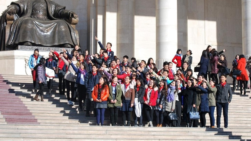 "In this Friday, Oct. 30, 2015 photo, Mongolia schoolchildren pose for photos near the Chinggis Khaan statue in front of the Mongolian Parliament House in Ulaanbaatar, Mongolia. Sandwiched between China and Russia, landlocked Mongolia has long tread a middle path, maintaining a balance between Moscow and Beijing while referring to the U.S., and other remote allies as ""third neighbors."" Now, with a wealth of mineral resources set to transform its largely agrarian economy, Mongolia is moving to cement that even-handed status by adopting permanent neutrality as a safeguard against outside dominance. (AP Photo/Ganbat Namjilsangarav)"