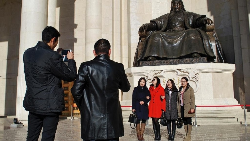 "In this riday, Oct. 30, 2015 photo, residents pose for photos near the Chinggis Khaan statue in front of the Mongolian Parliament House in Ulaanbaatar, Mongolia. Sandwiched between China and Russia, landlocked Mongolia has long tread a middle path, maintaining a balance between Moscow and Beijing while referring to the U.S., and other remote allies as ""third neighbors."" Now, with a wealth of mineral resources set to transform its largely agrarian economy, Mongolia is moving to cement that even-handed status by adopting permanent neutrality as a safeguard against outside dominance. (AP Photo/Ganbat Namjilsangarav)"