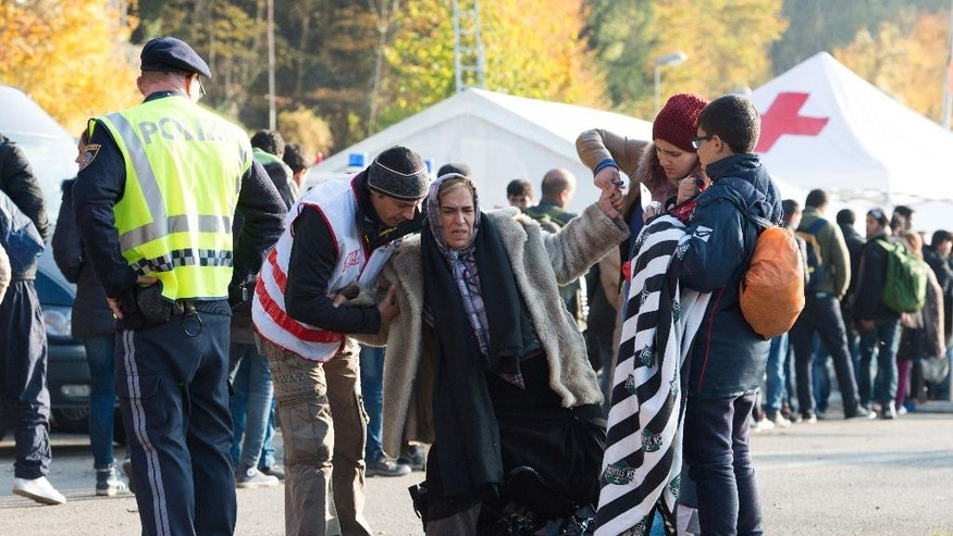 A Red Cross worker helps a Syrian family after crossing the border between Austria and Germany near Passau, Friday, Oct. 30, 2015. Germany is a preferred destination for migrants and has seen more arrivals than any other European Union country. About 577,000 people seeking asylum came to Germany from January to the end of September this year, authorities say. (Sebastian Kahnert/dpa via AP)