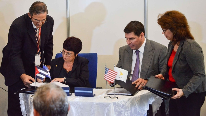 President and CEO at Sprint Corporation Marcelo Claure and Cuban Director of Mobile Services at ETECSA company Hilda Arias sign bilateral agreements on November 2, 2015.