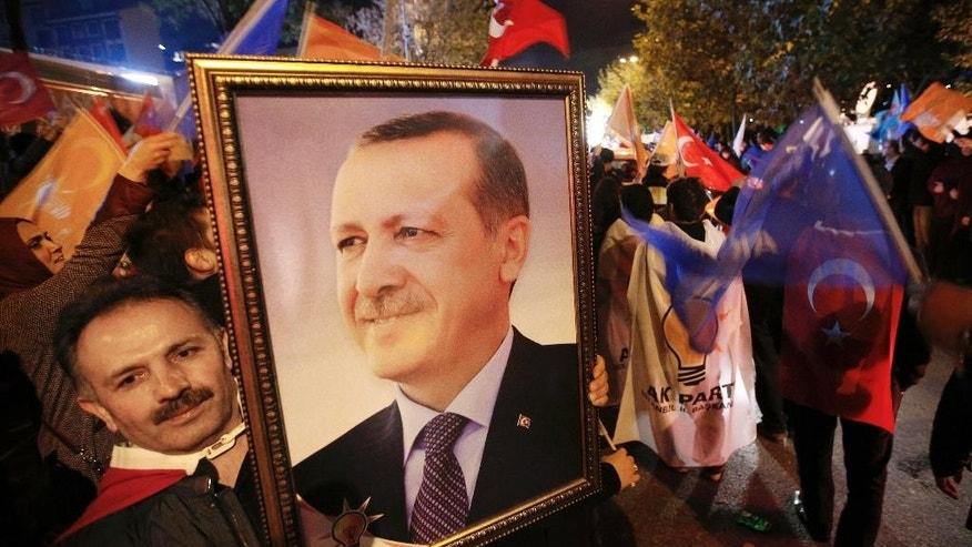 A supporter of the Justice and Development Party, (AKP), holds a portrait of Turkey's President Recep Tayyip Erdogan as people celebrate outside the AKP headquarters, in Istanbul, Turkey, late Sunday, Nov. 1, 2015. Turkey's ruling party secured a stunning victory in Sunday's snap parliamentary election, sweeping back into single-party rule only five months after losing it. The preliminary result, reported after nearly 99 percent of votes were counted, would show the ruling Justice and Development Party (AKP) had won more than 49 percent of the vote and was projected to get 316 seats in parliament, in a stunning victory. (AP Photo/Emrah Gurel)