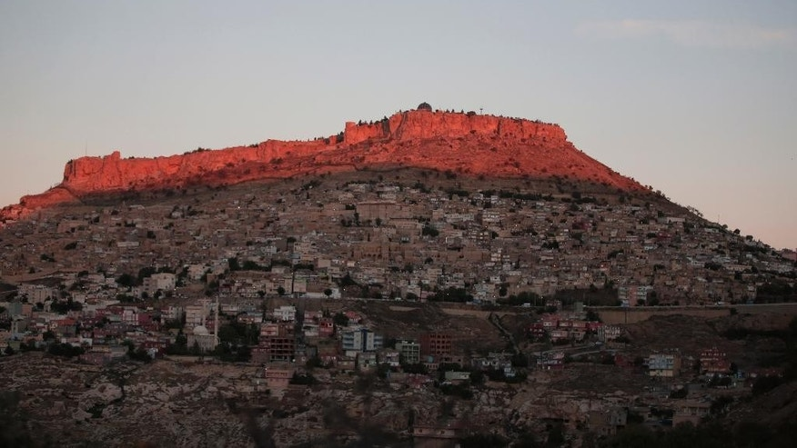 As it rises, the sun lights the historic Mardin Castle over the old city in Mardin, in Turkey's predominantly Kurdish southeast, Sunday, Nov. 1, 2015. Turkey's ruling party secured a stunning victory in Sunday's snap parliamentary election, sweeping back into single-party rule only five months after losing it. The preliminary result, reported after nearly 99 percent of votes were counted, would show the ruling Justice and Development party (AKP) had won more than 49 percent of the vote and was projected to get 316 seats in parliament, in a stunning victory. (AP Photo/Lefteris Pitarakis)