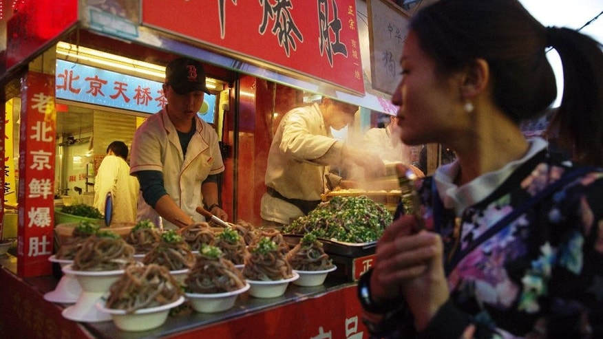 In this photo taken Thursday, Oct. 29, 2015, a street vendor sell local delicacies in Beijing, China. President Xi Jinping said Tuesday, Nov. 3, 2015 that China needs at least 6.5 percent economic growth in coming years and the Communist Party announced plans to let its tightly controlled yuan trade freely by 2020. (AP Photo/Ng Han Guan)
