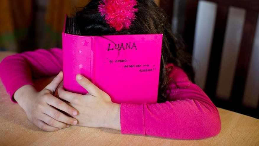 In this Sept. 29, 2015 photo, Luana hides behind her photo album at her home in Merlo, Argentina. Luana, who was born a boy, says she remembers her mom trying to make her a boy. Gabriela Mansilla, her mother, says the male reinforcement destroyed their family life. Manuel frequently banged his head against the wall. Patches of hair fell out. (AP Photo/Natacha Pisarenko)