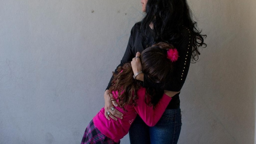 "In this Sept. 29, 2015 photo, Luana embraces her mother Gabriela Mansilla at home in Merlo, Argentina. Mansilla says there were always clear differences in her identical twins. Manuel, Luana's birth name, wore shirts on his head, apparently imitating long hair. He liked dolls. Princesses and mermaids were his favorite movie characters. Among his first words: ""I girl."" (AP Photo/Natacha Pisarenko)"