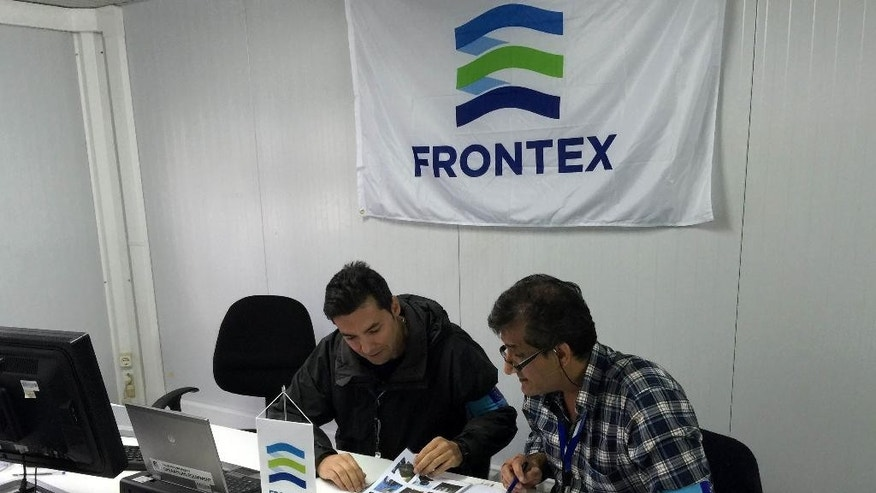 In this photo taken on Saturday, Oct. 31, 2015, Frontex officer Francisco Ramos, left, and a colleague review data at a registration center run by the EU border protection agency at Moria on the island of Lesbos in southeastern Greece. The pilot program on Lesbos is aimed at speeding up registration of migrants and refugees amid a surge in the daily arrivals on Greek Islands. (AP Photo/Derek Gatopoulos)