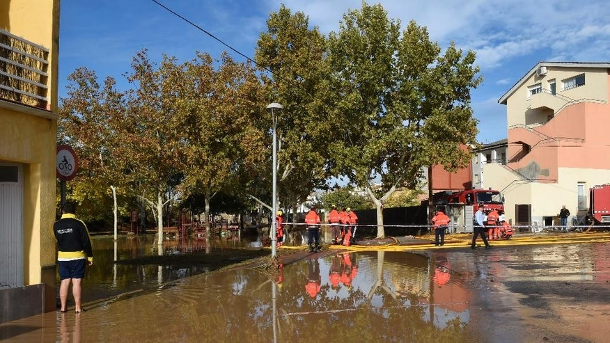 Emergency workers attended the scene where five residents were rescued and hospitalized after the rain engulfed a ground floor of the building next to the Sio River in the town of Agramunt, in Lerida province, Spain, Tuesday, Nov. 3, 2015. A river in northeastern Spain swelled by torrential downpours overflowed its banks early Tuesday morning, inundating a nursing home and killing four elderly residents, authorities said. (AP Photo/Santi Iglesias)