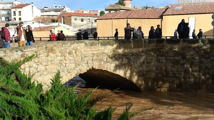 People look at the Sio River near to the building where five residents were rescued and hospitalized after the rain engulfed a ground floor of the building in the town of Agramunt, in Lerida province, Spain, Tuesday, Nov. 3, 2015. A river in northeastern Spain swelled by torrential downpours overflowed its banks early Tuesday morning, inundating a nursing home and killing four elderly residents, authorities said. (AP Photo/Santi Iglesias)