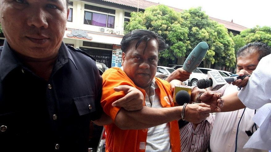"Handcuffed Indian fugitive Rajendra Sadashiv Nikalje, known in India as ""Chotta Rajan,"" center, is escorted by plain-clothed police officers for questioning in Bali, Indonesia, Tuesday, Nov. 3, 2015. The alleged organized crime boss, wanted for  involvement in several mafia killings and other major crimes in his homeland, was arrested last week after arriving at Bali's airport from Sydney based on information from Interpol and Australian authorities. (AP Photo/Firdia Lisnawati)"