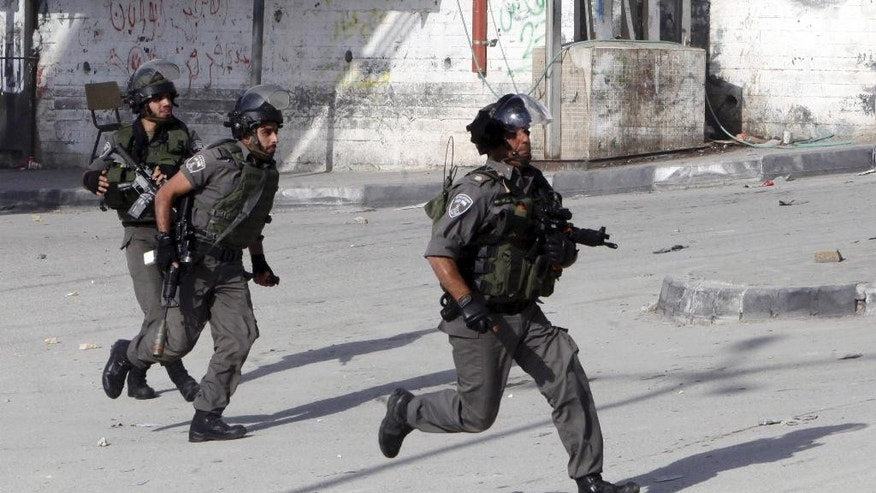 Israeli border police run during clashes with Palestinian students  in Abu Dis,West Bank, Monday, Nov. 2, 2015.  A series of Palestinian attacks linked to tensions over a sensitive Jerusalem holy site began in mid-September. In addition to the near-daily attacks, violent demonstrations have erupted in Israel, the West Bank and Gaza, with Palestinian stone-throwers clashing with Israeli troops. (AP Photo/Mahmoud Illean)