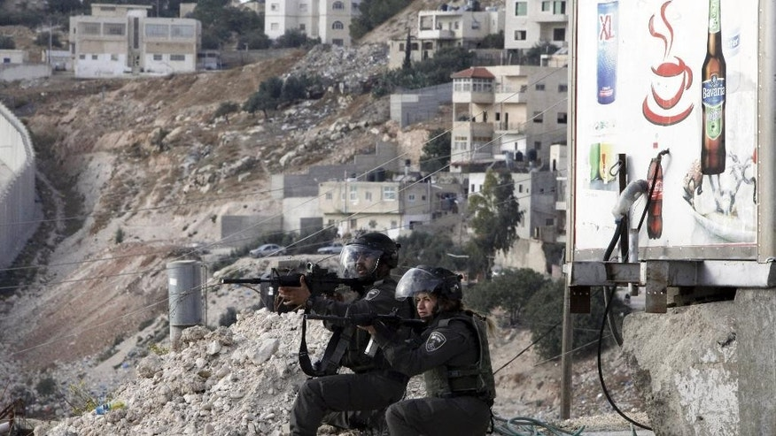 Israeli border policemen aim their weapons during clashes with Palestinian students  in Abu Dis,West Bank, Monday, Nov. 2, 2015.  A series of Palestinian attacks linked to tensions over a sensitive Jerusalem holy site began in mid-September. In addition to the near-daily attacks, violent demonstrations have erupted in Israel, the West Bank and Gaza, with Palestinian stone-throwers clashing with Israeli troops. (AP Photo/Mahmoud Illean)