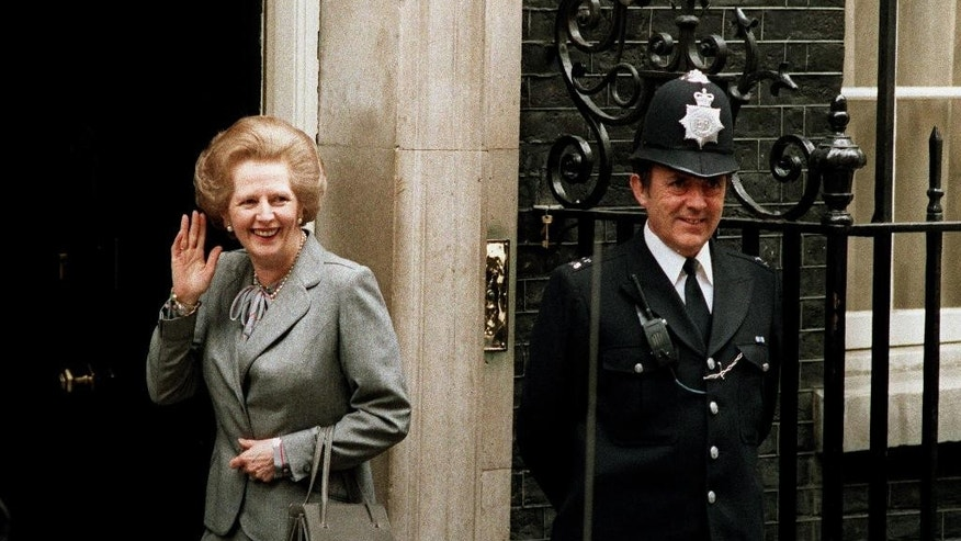 FILE - In this May 11, 1987 file photo, Britain's Prime Minister Margaret Thatcher waves to members of the media on returning to No. 10 Downing Street from Buckingham Palace after a visit with Queen Elizabeth II. Christie's is set to sell personal possessions of late British Prime Minister Margaret Thatcher, including papers, mementoes, clothes _ and her iconic handbags. The auctioneer said Tuesday, Nov. 3, 2015 that 150 lots will go under the hammer Dec. 15 in London, with another 200 sold by online auction.  The suit worn in this photo will be included in the auction.  (AP Photo/Dennis Redman, File)