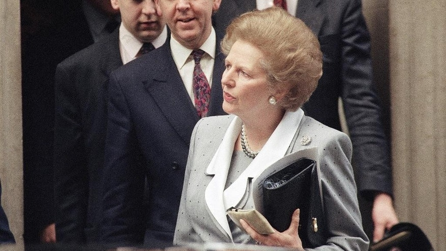 FILE - In this March 15, 1990 file photo,  Britain's Prime Minister Margaret Thatcher leaves 10 Downing Street in London en route to the House of Commons. Christie's is set to sell personal possessions of late British Prime Minister Margaret Thatcher, including papers, mementoes, clothes _ and her iconic handbags. The auctioneer said Tuesday, Nov. 3, 2015 that 150 lots will go under the hammer Dec. 15 in London, with another 200 sold by online auction. (AP Photo/Peter Kemp, File)
