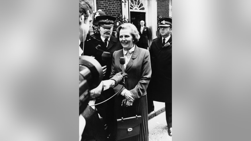 FILE - In this May 4, 1979 file photo, Britain's newly elected Prime Minister Margaret Thatcher talks to the press as her husband Denis waits on the doorstep of  10 Downing Street, in London, Christie's is set to sell personal possessions of late British Prime Minister Margaret Thatcher, including papers, mementoes, clothes _ and her iconic handbags. The auctioneer said Tuesday, Nov. 3, 2015 that 150 lots will go under the hammer Dec. 15 in London, with another 200 sold by online auction.  The suit worn in this photo will be included in the auction. (AP Photo, File)